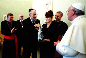 Presentation of gift to Pope Francis: left to right - Kurt Cardinal Koch, president of the Pontifical Council for Promoting Christian Unity; Martin Budd, Treasurer, IJCIC; Lawrence Schiffman, Chair, IJCIC; Betty Ehrenberg, Vice Chair, IJCIC; assistant to the Pope Archbishop Ganswein; Pope Francis. (PRNewsFoto/World Jewish Congress)