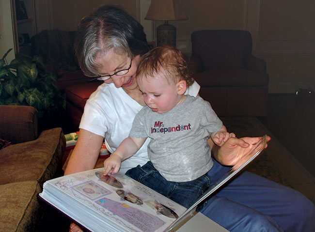Audrey Polt shows her grandson Samuel his personal scrapbook album.