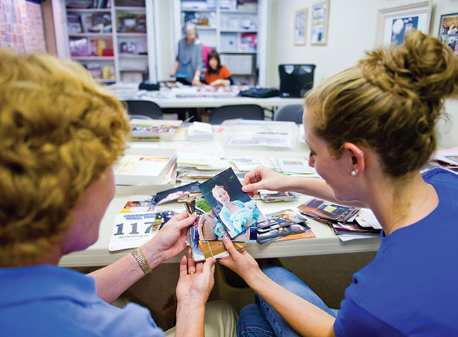 Megan Molitoris and mother Carol Saucier select photos for an album they are working on together.