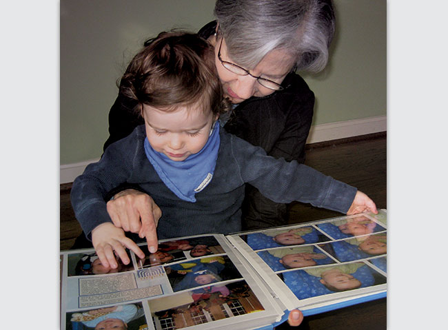 Audrey Polt shows her grandson Ethan his personal scrapbook album.