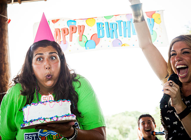 Camp Director Dori Zvili blows out a birthday cake candle during Milldale's celebration.