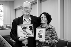 "Rabbi Yerachmiel Shapiro calls the Parkers, shown here holding photos of their adopted children, ""heroes."""