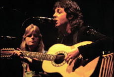 "Former Beatle Paul McCartney performs ""Getting Better"" in 1976.  His ex-wife, Linda, is also pictured. (Jim Summaria via Wikimedia Commons)"