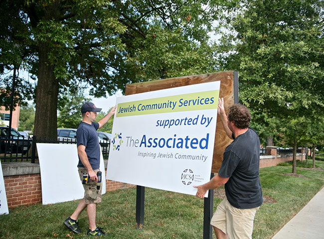 Professionals from Just Posters  erect one of 68 new Associated signs.