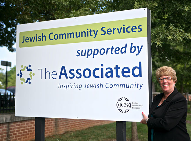 Executive Director Barbara Gradet stands before the Jewish Community Services lawn sign. JCS is one of The Associated's 14 agencies.