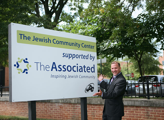 Barak Hermann, the new Jewish Community Center president, enjoys a warm summer day, pointing to his new lawn sign.