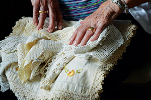 Frieda Pertman, 96, who lost her parents and six siblings to the Holocaust, displays her aunt's more-than-100-year-old crocheted lace. At right, Frieda  at 26 in Russia with son Allan, daughter Rita and late husband Chaim.