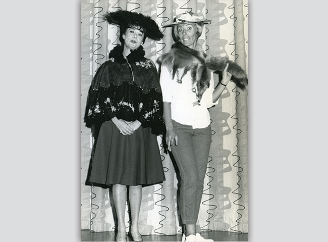 Two women in costume enjoy Rose Greenberg's retirement party, 1974.
