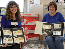 Special education teacher Janna Freishtat (left) and English teacher Cyndie Fagan have been instrumental in moving the Six Million Stamps Project forward. Shown here, they sit with a tub of thousands of stamps, many still waiting to be processed. (Photo by Melissa Gerr)