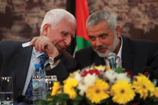 Head of Hamas Ismail Haniyeh (right) and senior Fatah official Azzam Al-Ahmed share a private moment during a news conference that announced a Palestinian reconciliation agreement in Gaza City on April 23. (Abed Rahim Khatib /Flash90)