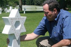 Glenn Marcus spends a somber moment at the grave of his uncle, Milton, at Lorraine  American Cemetery in France. (Provided)