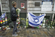 A Jewish boy places flowers in front of the Jewish Museum in Brussels, Belgium in memory of the four victims of a recent shooting.  (ANTHONY DEHEZ/AFP/Getty Images/Newscom)