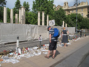 Passers-by look at Holocaust-related memorabilia left by citizens who are protesting the monument to the 1944 German occupation. (Ruth Ellen Gruber)