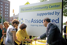 (From left): Lainy LeBow-Sachs, president of the BJC, Linda Hurwitz, chair-elect of The Associated, and Jason Blavatt, co-chair of The Associated's Israel and Overseas Committee, tie three yellow ribbons around the Weinberg Park Heights JCC's sign.  (Provided)