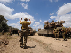 An Israeli soldier directs a Merkava tank at an army deployment area near Israel's border with the Gaza Strip on July 17. (Gili Yaari/Flash90)
