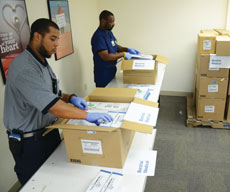 Dandre Wallace (left), materials specialist, and Sean Brunson, coordinator of surgical supply, pack up surgical gloves, needles, syringes, surgical sponges, skin staplers and other trauma medical equipment being sent to Barzilai Hospital, the  sister hospital of Sinai Medical Center in Baltimore, located in Ashkelon, Baltimore's sister city. (Melissa Gerr)