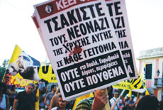 Anti-fascist protesters hold signs and a banner in front of the Athens  municipal amphitheater during a swearing-in ceremony for Golden Dawn party member Ilias Kasidiaris on Aug. 29.