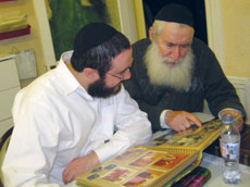 Rabbi Nachum Katsenelenbogen and his father, Moshe, look through a photo album of Moshe's days in Russia. (Provided)