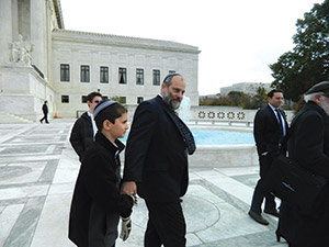 Ari Zivotofsky and his son  Menachem leave the Supreme Court Building after the justices debated Zivotofsky v. Kerry. (Photo by Suzanne Pollak)