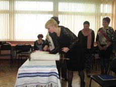 Irina uses a Torah from Project Kesher's Torah  Return Project.