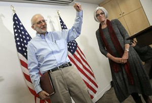 Alan Gross, freed from a Cuban prison earlier in the day, waves after concluding his remarks with his wife, Judy, at a news conference in Washington shortly after arriving in the United States, Dec. 17, 2014. (Win McNamee/Getty Images)