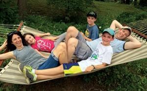Liz and Dan Spevack with children Ayelet, Noam and Eytan, on a hammock at Ramah Berkshires. The Spevacks met at Ramah Berkshires, where Dan Spevack's parents also met. All three children attend Ramah camps. (Courtesy of Liz Spevack)