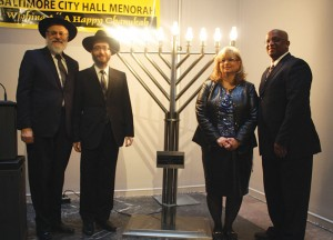 "Council President Bernard C. ""Jack"" Young (right), with the City Council's Jewish liaison, Betsy Gardner, Rabbis Chesky Tenenbaum and Shmuel Kaplan pose alongside the City Hall menorah.  (Provided)"