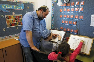 Knitted yarmulkes and pro-settler policies are not the face of religious Zionism after all. Here, Rabbi Eran Fletzki teaches children at a school in the West Bank settlement of Neve Daniel.