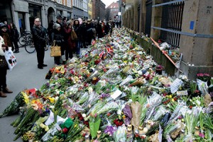 Flowers fill a street next to a synagogue in Copenhagen, where a Jewish guard was  killed on Saturday.