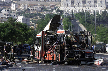 Israeli bomb experts search bus number 32 in Jerusalem's Pat junction near the neighborhood of Gilo June 18, 2002 after a Palestinian suicide bomber blew himself up, killing 17 people and wounding many others. (GIL COHEN MAGEN/REUTERS/Newscom)