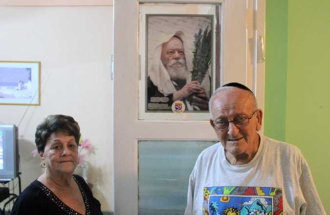 Rebeca and Alberto Meshulam, 70 and 78, respectively, in front of a portrait of the late Lubavitcher rebbe, Menachem Mendel Schneerson. The Meshulams host Lubavitch emissaries at their Havana apartment throughout the year. (Josh Tapper)