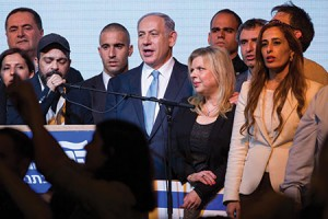 Israeli Prime Minister Benjamin Netanyahu, flanked by his wife and Likud Party supporters, has a lot of fence-mending to do. (Miriam Alster/Flash90)