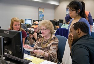 Accounting professor Susan Milstein helps students and a client with a simple tax return at McDaniel College's free tax assistance program. (Marc Shapiro)