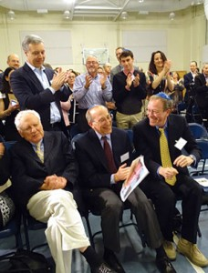From left: Alfred Moses, a former ambassador to Romania, and Robert and Bill Gottesman, of the Gottesman Fund, are applauded as Jewish Primary Day School officials announce that their gifts from Moses and The Gottesman Fund will enable Washington's only Jewish day school to add a middle school. (Provided)