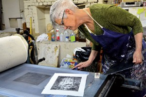 Artist Ruth  Channing inspects a print in her Mount Vernon studio. .
