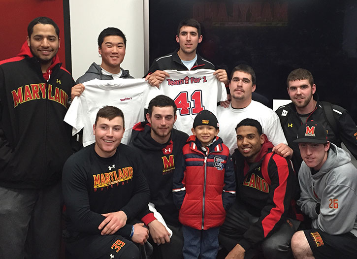 Ty Jones, a 7-year-old who suffers from neuroblastoma, poses with the University of Maryland, College Park, baseball team, which adopted him. (Provided)