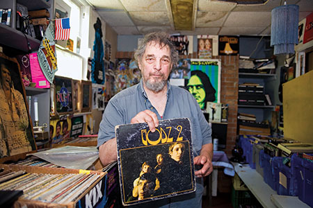 Larry Kessler holds The Godz's second album in his record shop. He is second from the right on the album cover.