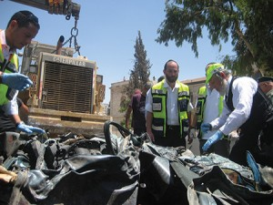 Yehuda-Meshi Zahav (right) and ZAKA volunteers assist at the site of a 2014 terrorist attack in Jerusalem. (ZAKA)