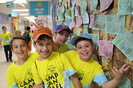 "Gan Israel campers happily pose for a photo by the ""kotel."""
