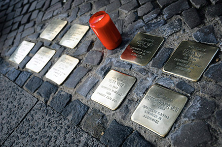 A candle stands among a set of stolpelsteine or stumbling stones in Frankfurt. The stones memorialize spots where Jews had lived before the Holocaust. (TILMAN VOGLER/EPA/Newscom)