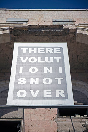 """A banner declaring """"The Revolution Is Not Over"""" greets museum visitors. (Photo by Marc Shapiro)"""