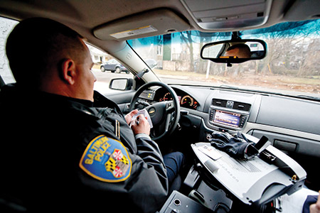 "Officer Jacob Gabbard patrols the Northwestern District. (Photo from the JT's ""A Night In The Life,"" ride-along article from January 2014. (Photo by David Stuck)"