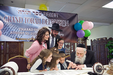 Chabad of Owings Mills Rabbi Nochum Katsenelenbogen and his family help Rabbi Moshe Klein, a scribe from New York, write one of the remaining letters in the Chabad's new Torah. (Photos by Marc Shapiro)