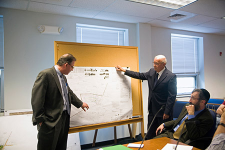 Ken Abel (left), who lives next to the site of the proposed synagogue, shows where his house is as attorney J. Carroll Holzer (standing) and Rabbi Velvel Belinsky look on.