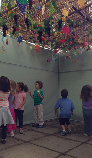 Preschoolers from the JCC help decorate a sukkah at Weinberg Park Assisted Living. (Provided)