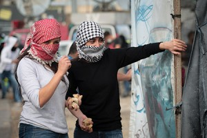 Masked Palestinian girls take a break while throwing stones during a clash with the Israeli army north of Ramallah. (Mohammad Alhaj/NurPhoto/Sipa USA/Newscom)