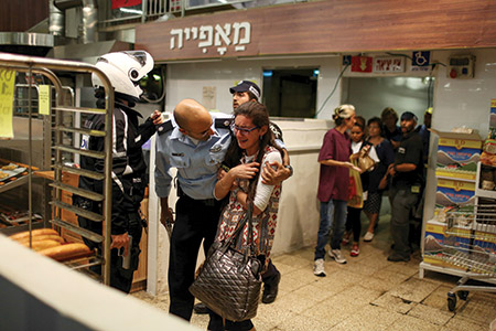 An Israeli soldier calms a bystander in the aftermath of a fatal Palestinian stabbing attack at Jerusalem's Central Bus Station earlier this month. Palestinians have claimed the violence is in response to a change in the status quo on the Temple Mount, which Israel vehemently denies. (NOAM MOSKOWITZ/REUTERS/Newscom)