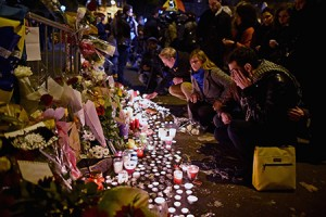 People place flowers and candles near the scene of the Bataclan concert Hall terrorist attack in Paris. (Jeff Mitchell/Getty Images)