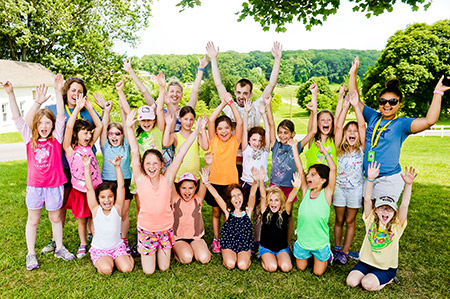 Beginning summer of 2016, the JCC is terminating Camp Milldale as its own program and instead, all J Day Camps campers will have access to the Milldale grounds in Reisterstown. In 2015, counselors from Odessa, Dima Garkavluk and Irina Gokhman (back row, center), enjoy time with the campers. (Photo by David Stuck)