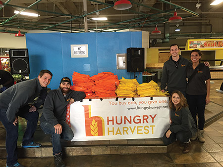 From left: Jon Heiber, chief strategy officer Mark Leybengrub, Emily Quade, co-founder and CEO Evan Lutz and Angela Parreco of Hungry Harvest are pictured at a free  farmers market, where residents of low-income neighborhoods can take home as  much produce as they want.